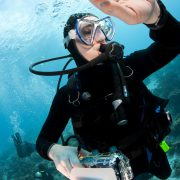 Scuba diver Elyn Stubblefield swimming over a tropical coral reef in Bonaire, Netherlands Antilles with her camera checking her dive watch during a safety stop.